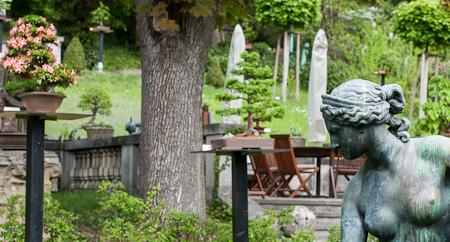 Skulptur blickt auf die Bonsai